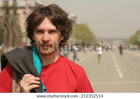 man in a red t-shirt/Man in red t-shirt standing outdoors and looking at the camera - stock photo