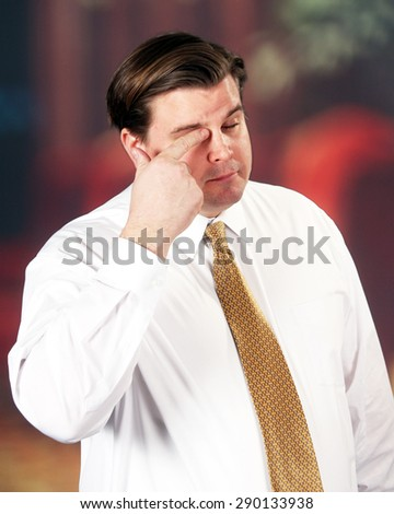 Man in a shirt and tie wiping his eye with his finger and a sad or pensive expression. - stock photo
