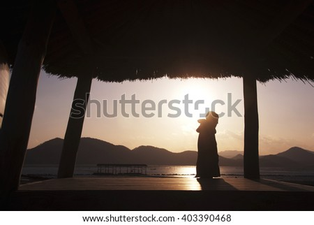 man in a small hut on the beach at sunset/man in a small hut on the beach at sunset - stock photo