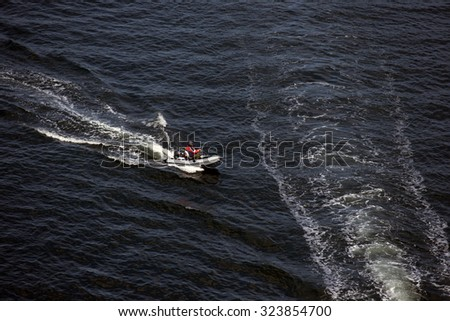 Man in a small inflatable boat are fishing in the sea - stock photo
