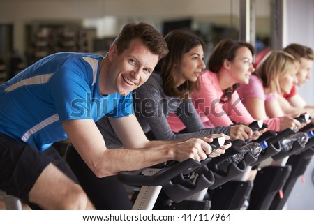 Man in a spinning class at a gym turning to smile at camera - stock photo