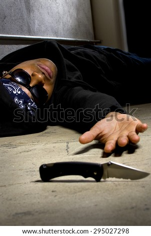 man in a street alley killed with a knife and victim of gang violence. the man is dying and laying on the ground. - stock photo