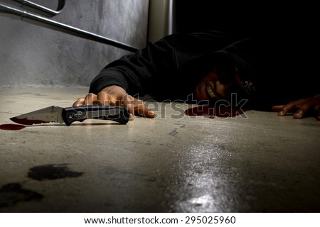 man in a street alley killed with a knife with blood and murder weapon. the man is laying dead or dying.  this version contains blood. - stock photo