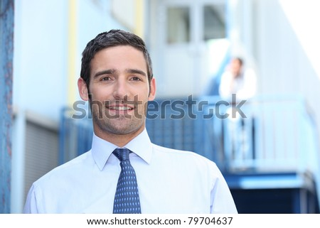 Man in a suit and tie outside his workplace