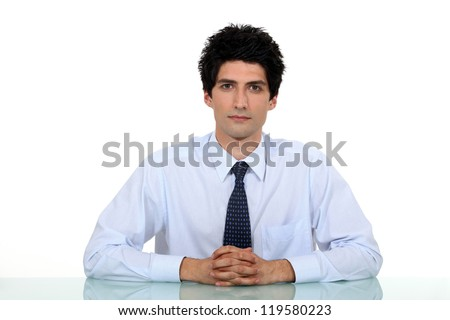 Man in a suit and tie sitting at a desk
