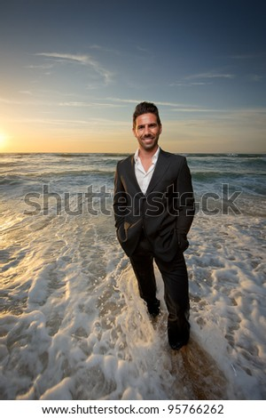 man in a suit at the beach on the water smiling