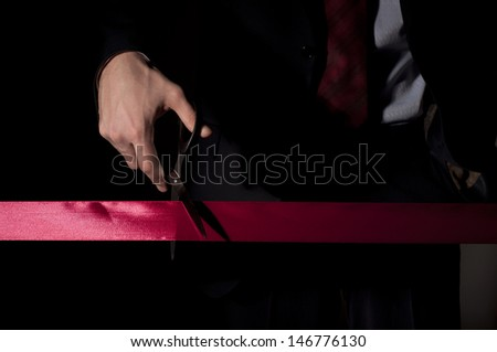 man in a suit, cuts a red tape, opening of event - stock photo