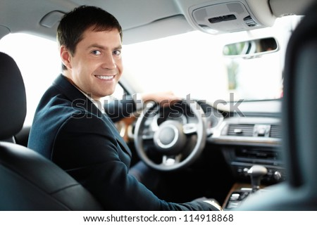 Man in a suit driving a car - stock photo