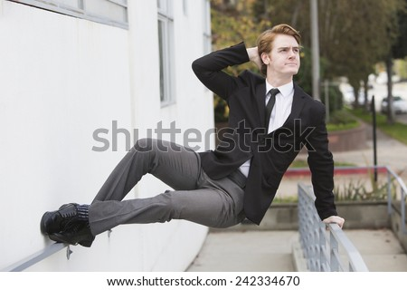 man in a suit jumping at a wall - stock photo
