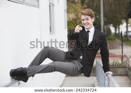 man in a suit jumping at a wall and pointing his finger - stock photo