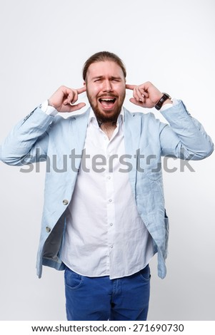 man in a suit on a white background, shouts, yells, insanity, covers his ears, does not want to hear, do not want to know - stock photo