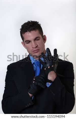 man in a suit putting on gloves getting ready for action - stock photo