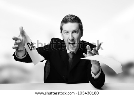man in a suit sat at a desk just ripped up  a  piece of paper up with the word debt printed on it and now throwing it away - stock photo