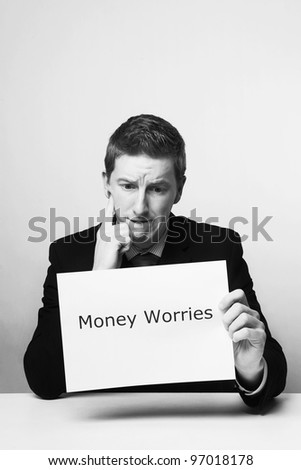 man in a suit sat at a desk look at a  piece of paper with the words money worries printed on it - stock photo
