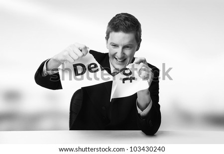 man in a suit sat at a desk ripping a  piece of paper up with the word debt printed on it and looking happy doing so. - stock photo