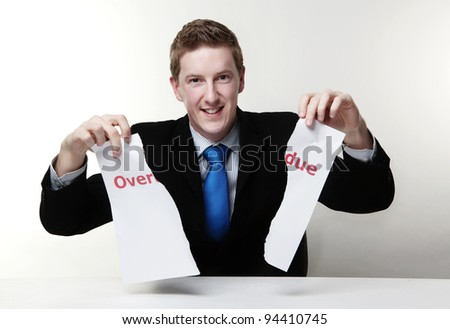 man in a suit sat at a desk ripping a  piece of paper up with the words overdue printed on it and looking happy doing so. - stock photo