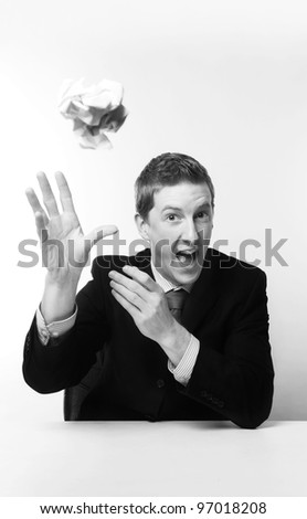 man in a suit sat at a desk throwing a ball of papper at you - stock photo