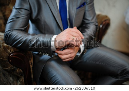 man in a suit sitting in a chair and puts cufflinks. - stock photo