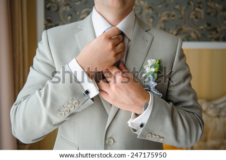 man in a suit straightens his tie with cufflinks on their sleeves. - stock photo