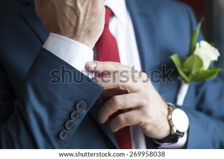 man in a suit with a tie groom buttonhole unbuttons his shirt