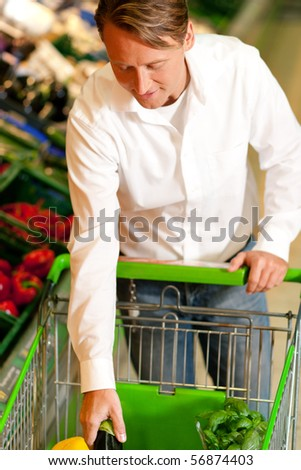 Man in a supermarket at the vegetable shelf shopping for groceries, he is putting some stuff into the shopping cart