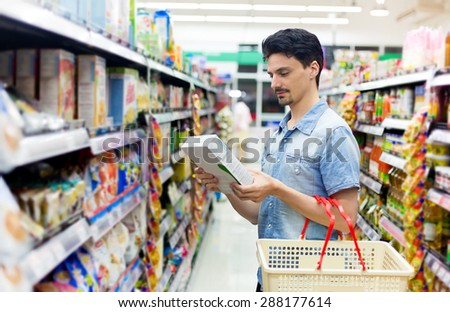 man in a supermarket buying a box of cornflakes - stock photo