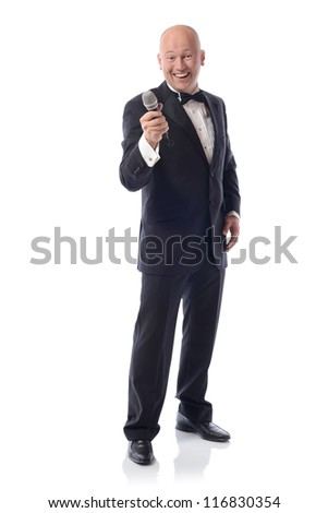 Man in a tuxedo offering microphone isolated on white - stock photo