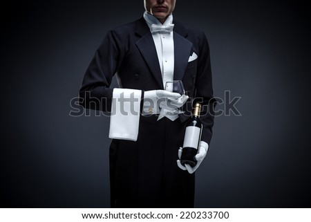 Man in a tuxedo with bottle and glass - stock photo