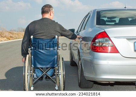Man in a wheelchair next to his car - stock photo