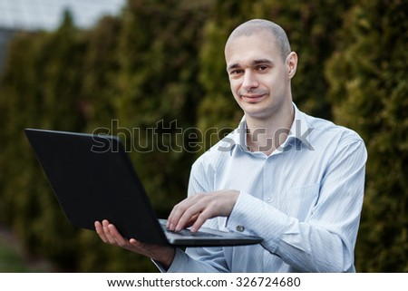 Man in a white shirt is holding a laptop on his arm.  His hand presses the button.