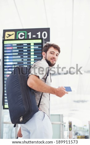 Man in airport holding his passport and hurrying for his flight near the schedule