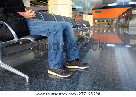 man in airport lounge sitting on chair and waiting for a plane - stock photo