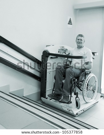 man in an invalid chair walks upstairs on the special elevating device - stock photo