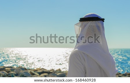 Man in Arab dress looks at the sea - stock photo