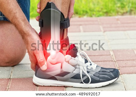 Man in athletic sneakers checking his ankle orthosis or brace on the street