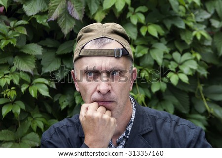 Man in backward baseball cap with displeased gaze, garden in the background - stock photo