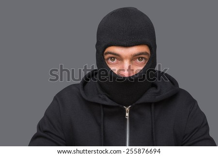Man in balaclava looking at camera on white background