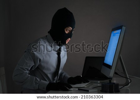 Man in balaclava stealing some information from the computer - stock photo