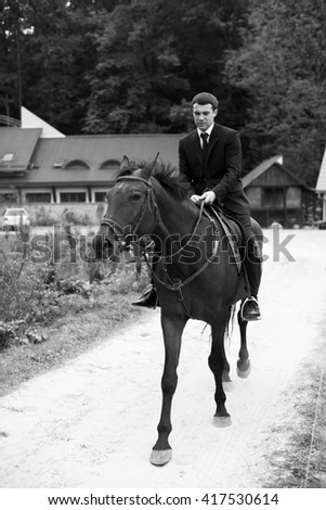 Man in balck suit rides a horse along the road