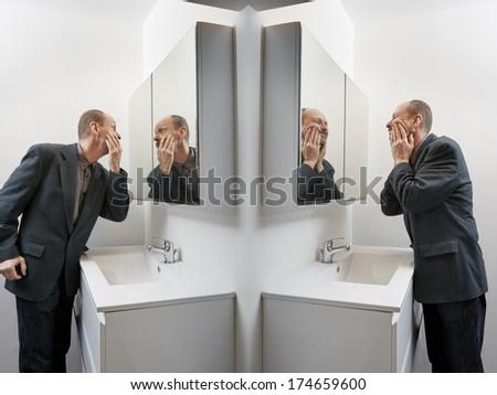 Man in bathroom applying cosmetics on his face - stock photo