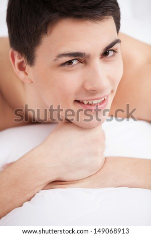 Man in bed. Handsome young man lying on bed and smiling