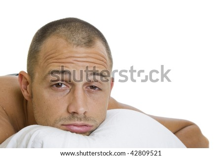 Man in bed trying to sleep with a pillow - stock photo