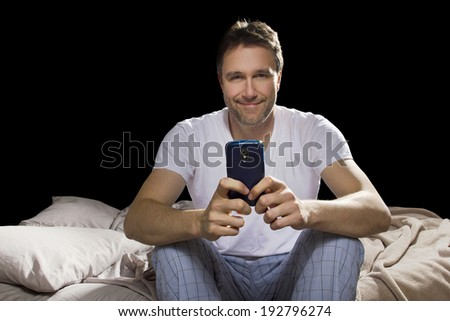 man in bedroom using cell phone late at night  - stock photo