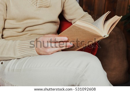 Man in beige jeans and sandy sweater reading book at home. Man in casual wear with book in hands.