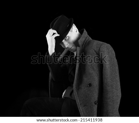 Man in black hat amd coat at the age of forty-six years old put his hand on his hat looking at the camera  on black  background  - stock photo