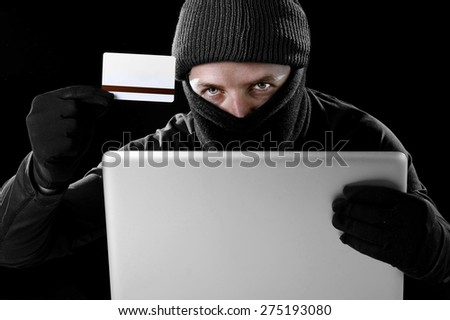 man in black holding credit card using computer laptop for criminal activity hacking password and private information cracking password too access bank account data in cyber crime concept - stock photo