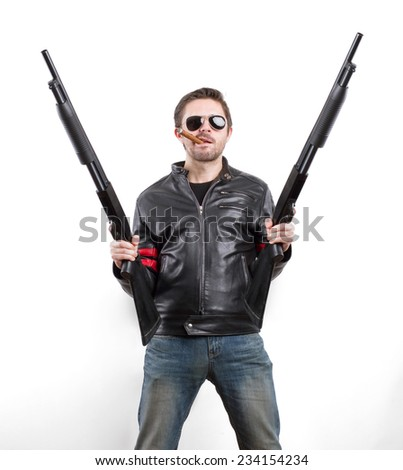 Man in black leather jacket and sunglasses with two shotguns - stock photo