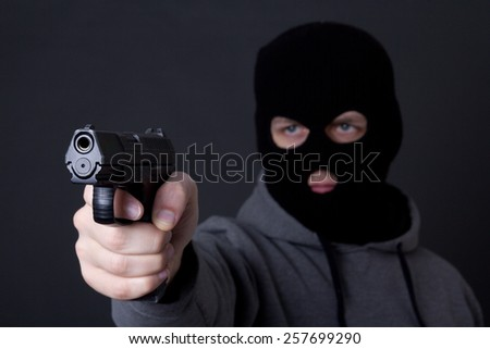 man in black mask aiming with gun over grey background - stock photo