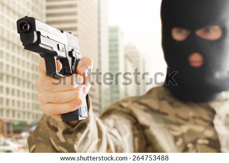 Man in black mask holding gun and city on background - stock photo