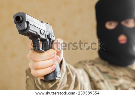 Man in black mask holding gun and ready to shot - stock photo